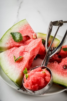 Summer fruit desserts, frozen cocktails. ice cream granite from watermelon with mint, one scoop in spoon for ice cream, on plate with slices of watermelon.