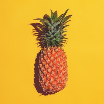 Summer fruit. pineapple on bright yellow background.