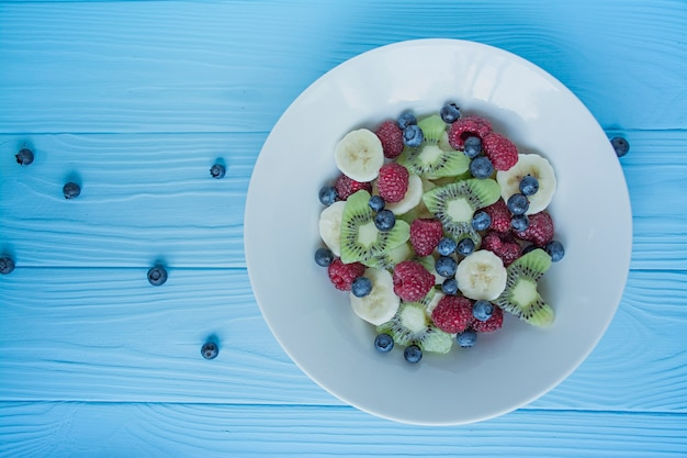 Summer fruit salad with kiwi, raspberries, banana, blueberries. vegetarian dish. view from above.