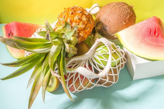 여름 과일 쇼핑 배경입니다. 신선한 열대 과일이 가득한 친환경 쇼핑백