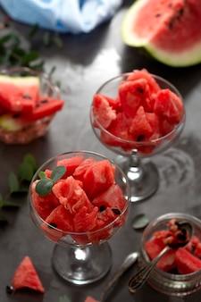 夏の果物、スナック。ガラスカップに新鮮なスイカのスライス。健康的でジューシーなフルーツ。