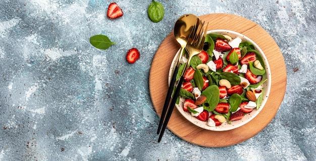 Летние фрукты клубника, шпинат салат с грецкими орехами, бальзамический уксус из сыра фета, капуста. в тарелке. концепции здорового питания