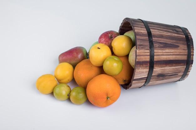 Летние плоды перемешивают из деревянного ведра.