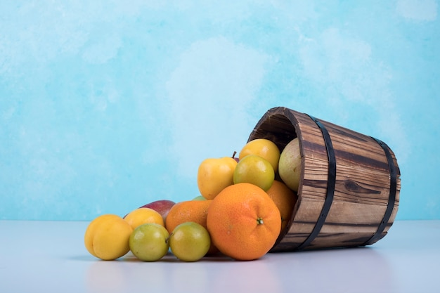 Summer fruits mix out of a wooden bucket on blue