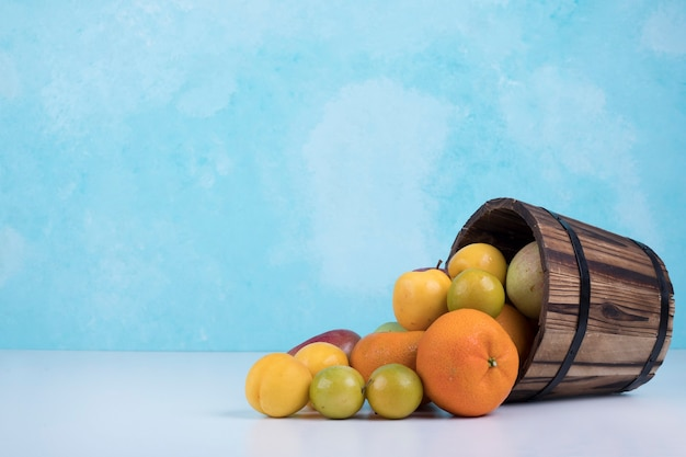 Summer fruits mix out of a wooden bucket on blue.