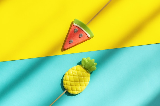 Summer fruits pineapple and watermelon lollipops on blue yellow background with hard light and shadow