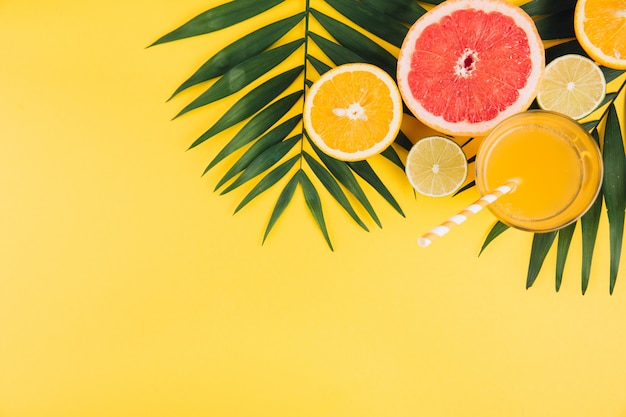 Summer fruits. tropical palm leaves, lime, grapefruit, orange and glass of juice on yellow background.