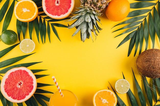 夏の果物熱帯のヤシの葉、パイナップル、ココナッツ、グレープフルーツ、オレンジ、黄色の背景にジュースのガラス。