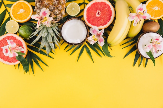 Summer fruits. tropical palm leaves, pineapple, coconut, grapefruit, orange and bananas on pink background.