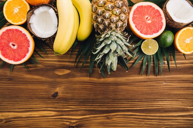 Summer fruits. tropical palm leaves, pineapple, coconut, grapefruit, orange and bananas on wooden background.