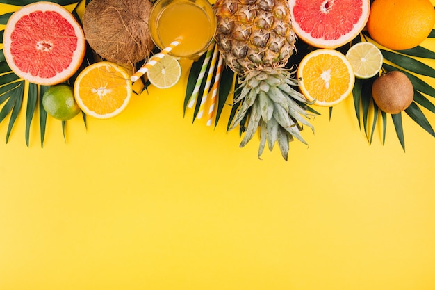 Summer fruits. tropical palm leaves, pineapple, coconut, grapefruit, orange and glass of juice on yellow background.