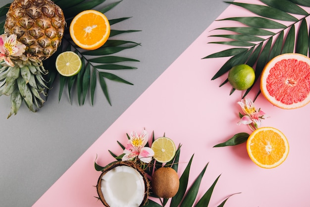 Summer fruits. tropical palm leaves, pineapple, coconut, grapefruit, orange and lime on pink background.