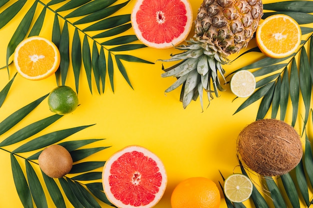 Summer fruits. tropical palm leaves, pineapple, coconut, grapefruit, orange and lime on yellow background.