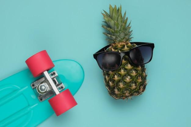 夏の楽しいコンセプト。ユーモアフラットレイ。クルーザーボードと青い背景のサングラスとパイナップル