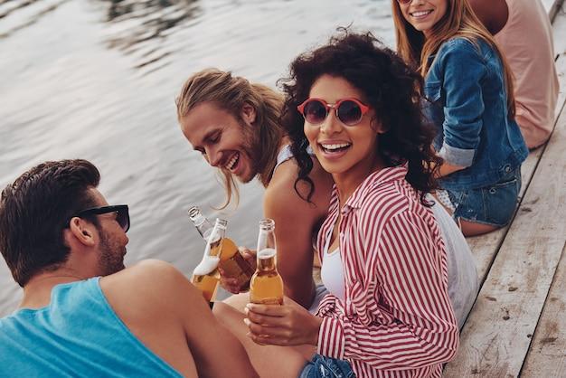 夏の楽しみ。桟橋に座って笑顔でクマを飲むカジュアルな服装で幸せな若者のグループ