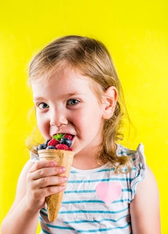 Summer fun holiday concept, cute blonde toddler girl eating berries from waffle ice cream cone, bright yellow  background
