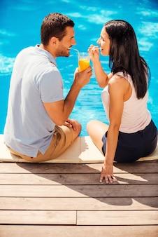 Летнее веселье. вид сверху счастливой пары в повседневной одежде, сидящей у бассейна и пьющей коктейль из одного стакана