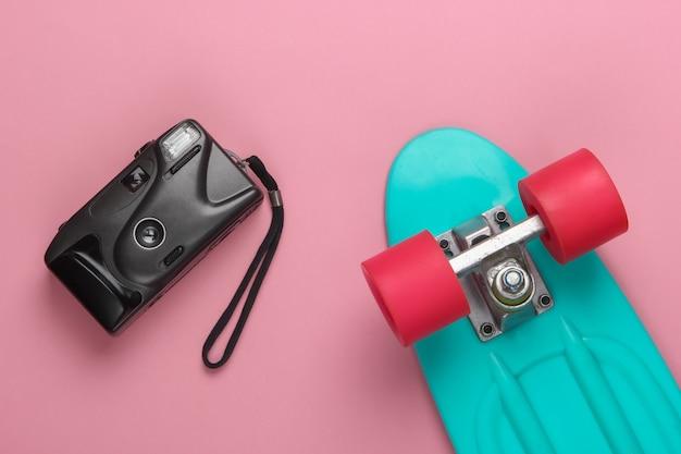 夏の楽しみ。ユースフラットレイ。ピンクのパステルカラーにレトロなカメラが付いたクルーザーボード。