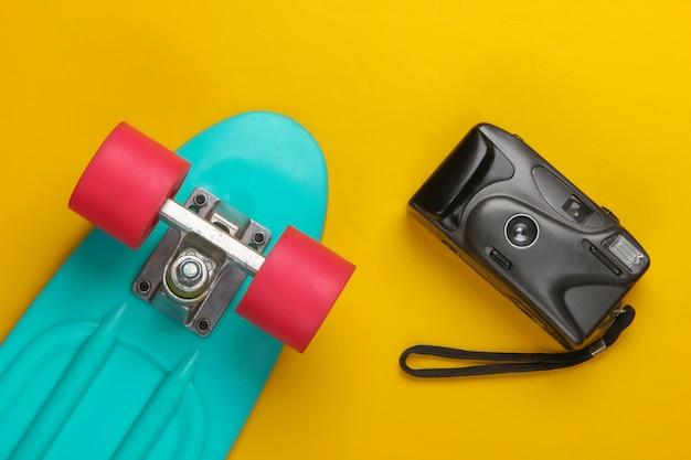 夏の楽しみ。ユースフラットレイ。黄色のレトロなカメラとクルーザーボード。