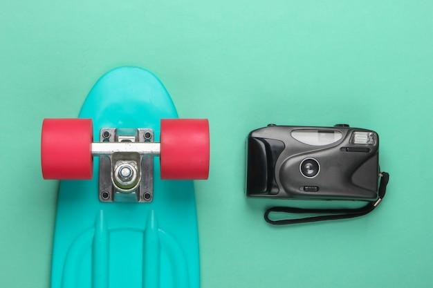 夏の楽しみ。ユースフラットレイ。ブルーパステルカラーのレトロなカメラ付きクルーザーボード。