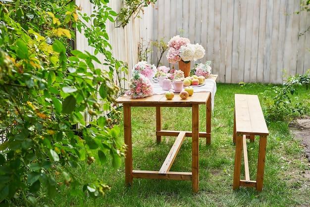 여름 정원 배경입니다. 테이블에 꽃 수국과 차 한잔. 좋은 아늑한 아침입니다. 자연에서 피크닉입니다. 어머니의 날 인사말 카드입니다. 축하