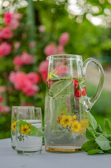In the summer garden of a country house. have a nice summer weekend, relax. soft drink (lemonade) with mint and mint leaves, a healthy product