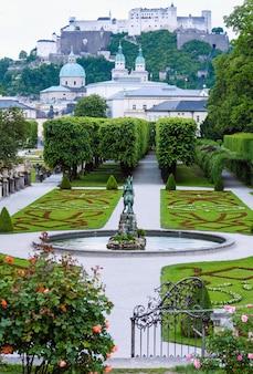 꽃이 만발한 잔디밭과 뒤에 호엔 잘츠부르크 요새가있는 미라벨 궁전의 여름 정원 (오스트리아 잘츠부르크)