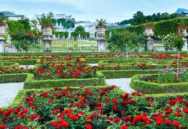 빨간 장미 화단과 뒤에 호엔 잘츠부르크 요새가있는 미라벨 궁전의 여름 정원 (오스트리아 잘츠부르크)