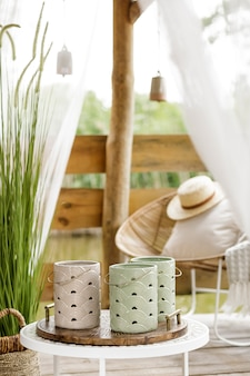Summer gazebo by the lake with stylish rattan armchair coffee table pillows plaid and elegant accessories in modern decor summer vibes chillout