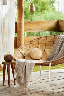 Summer gazebo by the lake with stylish rattan armchair, coffee table, sofa, pillows, plaid and elegant accessories in modern decor. summer vibes. chillout.