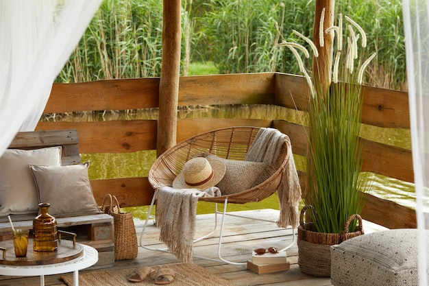 Summer gazebo by the lake with stylish rattan armchair, coffee table, sofa, pillows, plaid and elegant accessories in modern decor.