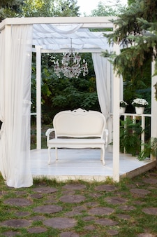 Summer gazebo with white curtains. alcove there is terrace on which a white sofa in style of provence or rustic.