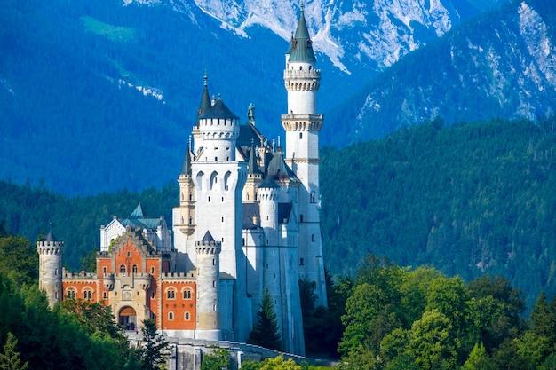 Летняя германия. солнечное утро. горы покрыты лесом. замок нойшванштайн