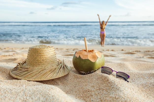 Летняя девушка в расфокусировке из океана на песке лежит в шляпе, солнцезащитных очках и кокосовом орехе.