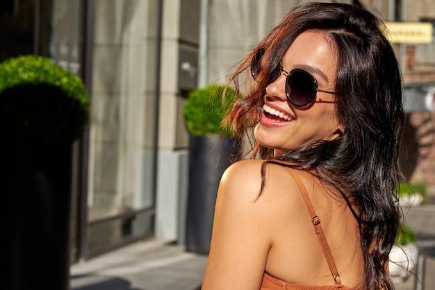 여름 소녀입니다. 안경을 쓰고 카메라를 보며 웃고 있는 젊은 백인 여성의 초상화는 도시 거리에 서서 좋은 날씨를 즐기고 있습니다. 사람들의 라이프 스타일과 패션 개념