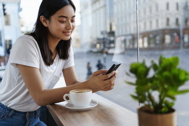 Summer girl sitting in cafe with cup of coffee, messaging on smartphone.
