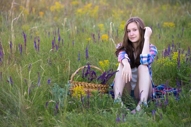 Лето. девушка-подросток сидит в одиночестве на лугу. возле корзины с шалфеем
