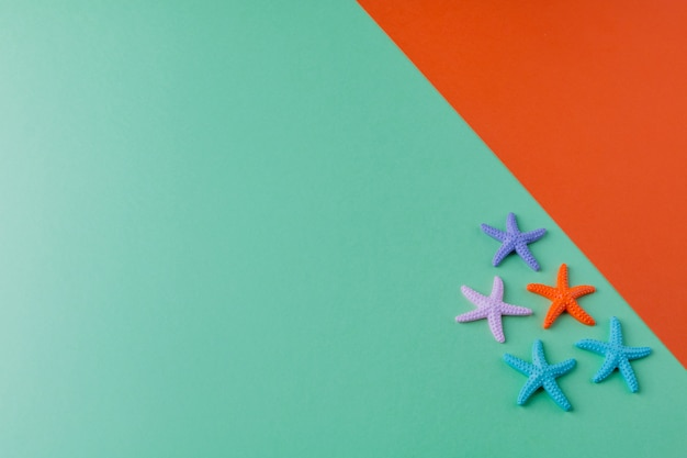 Summer  of green and orange paper with small coloured starfish. summer holidays and travel  flat lay. copyspace