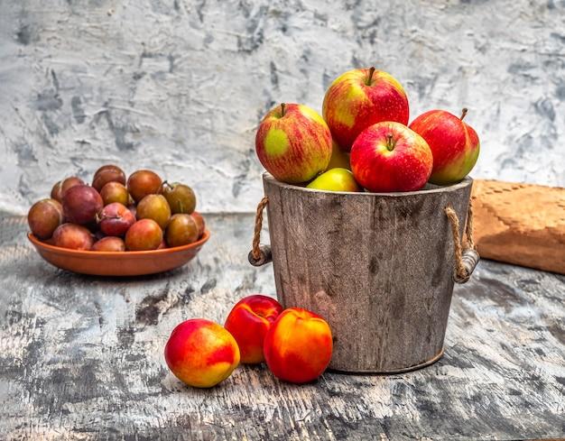 Летний урожай фруктов яблоки в деревянном ведре нектарины и сливы
