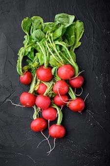 Летом заготавливают красную редьку. выращивание органических овощей. большой букет сырых свежих сочных редис на черном камне