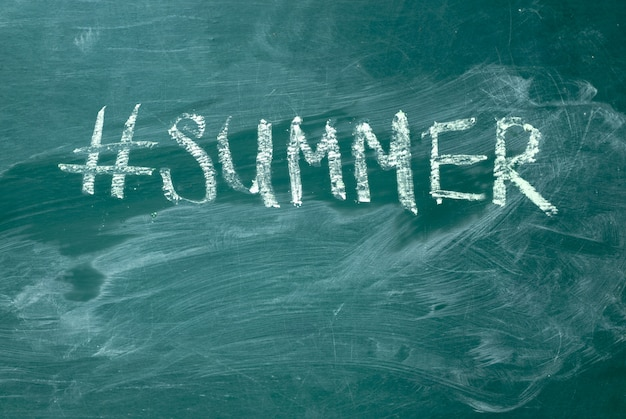 Summer hashtag it handwritten with white chalk on a green blackboard.
