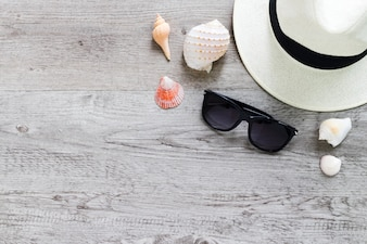 Summer hat and sunglasses on wooden table