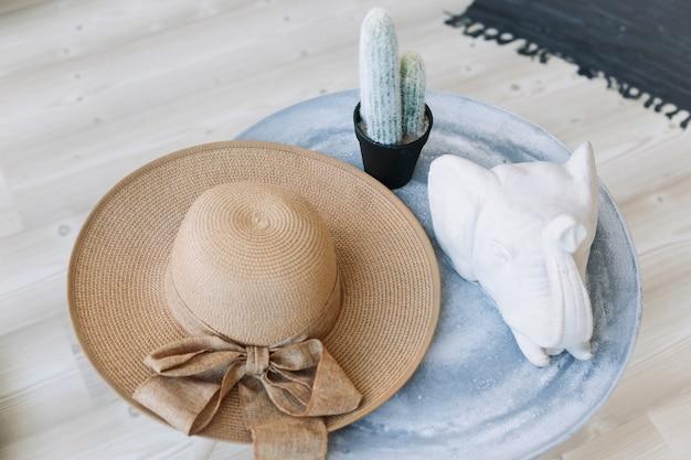 Летняя шляпа кактус и фигурка слона на столе в помещении экзотические элементы дизайна интерьера в стиле бохо