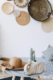 Летняя шляпа кактус и фигурка слона на столе в помещении элементы дизайна интерьера