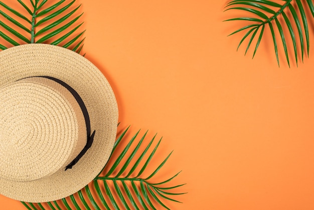 夏の帽子はオレンジ色の背景に緑の葉の上に横たわっていた。スペースをコピーします。