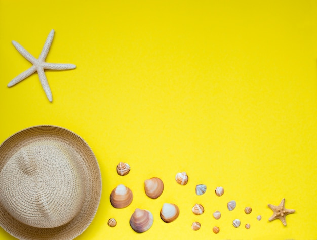 Summer hat and a selection of seashells and starfish, located on yellow.