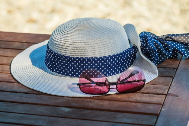 Summer hat and sunglasses isolated on wooden table.