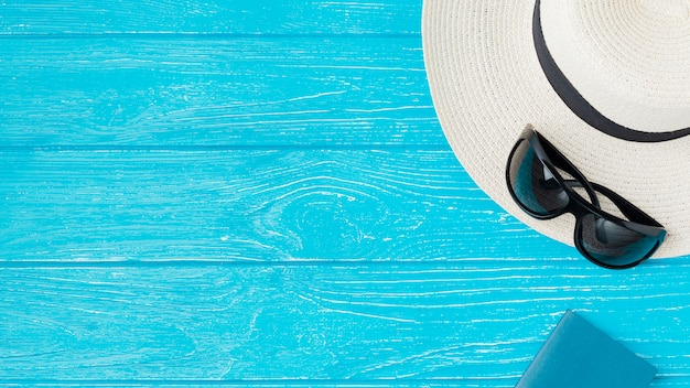 Summer hat and sunglasses near notebook on board