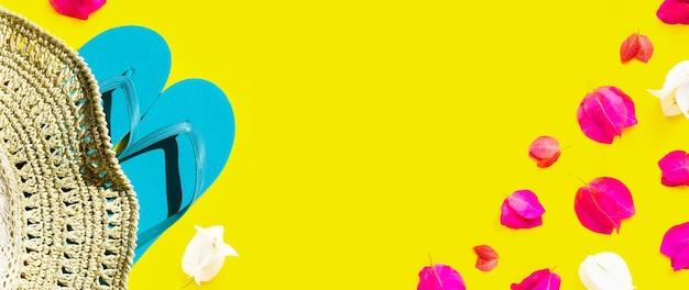노란색 표면에 파란색 플립 플롭과 부겐빌레아 꽃과 여름 모자