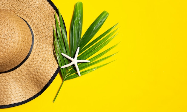 Summer hat with starfish on tropical palm leaves with  on yellow background. top view